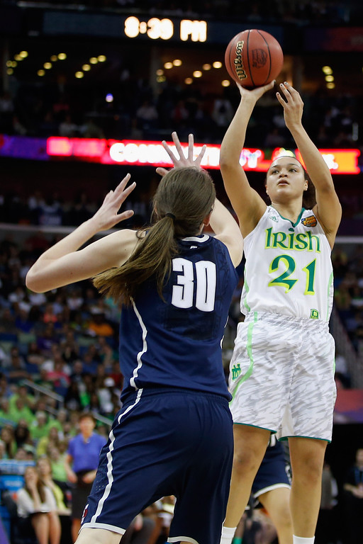 Description of . Kayla McBride #21 of the Notre Dame Fighting Irish makes a shot over Breanna Stewart #30 of the Connecticut Huskies during the National Semifinal game of the 2013 NCAA Division I Women\'s Basketball Championship at the New Orleans Arena on April 7, 2013 in New Orleans, Louisiana.  (Photo by Chris Graythen/Getty Images)