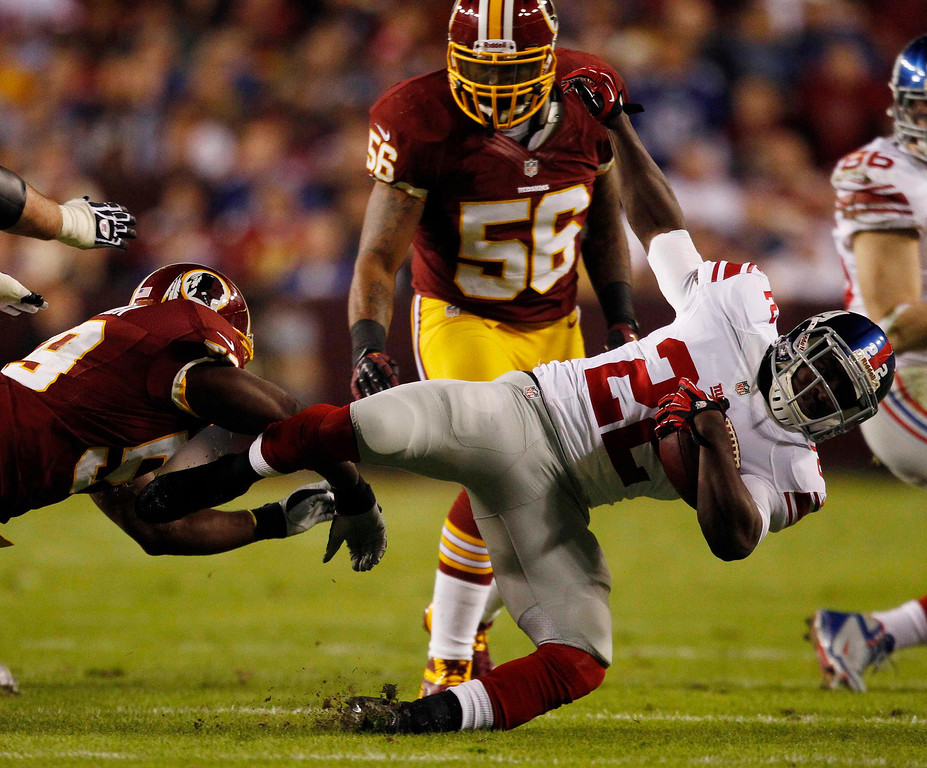 Description of . Washington Redskins linebacker London Fletcher (L)  tackles New York Giants running back David Wilson (R) during the first half of their NFL football game in Landover, Maryland December 3, 2012.  REUTERS/Gary Cameron