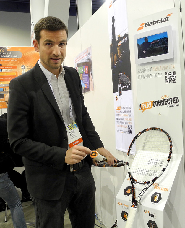 Description of . Thomas Otton, global communications director for the French racquet maker Babolat, shows the company's connected tennis racquet at the Consumer Electronics Show in Las Vegas on January 10, 2014.