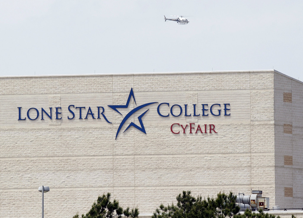 Description of . A police helicopter circles above the Cy-Fair campus of Lone Star Community College in Cypress, Texas, where officials say about a dozen people have been wounded in a stabbing attack Tuesday, April 9, 2013.(AP Photo/Houston Chronicle, Melissa Phillip)
