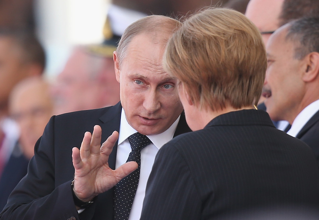 Description of . Russian President Vladimir Putin and German Chancellor Angela Merkel attend the main international ceremony with 17 heads of state at Sword Beach on June 6, 2014 at Ouistreham, France.   (Photo by Sean Gallup/Getty Images)