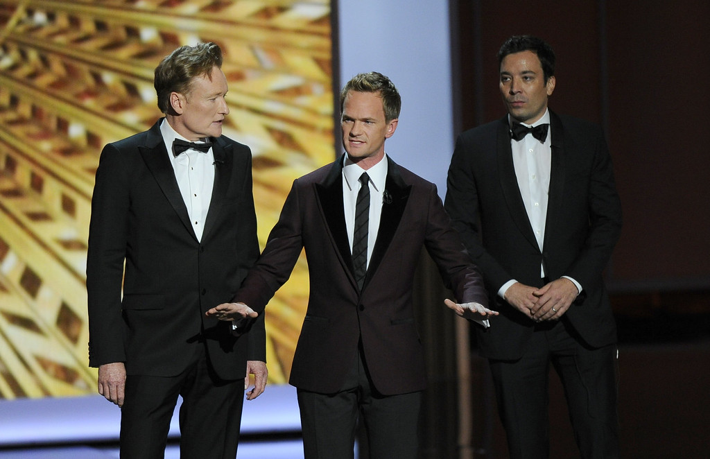 Description of . Conan O'Brien, from left, Neil Patrick Harris, and Jimmy Fallon speak onstage at the 65th Primetime Emmy Awards at Nokia Theatre on Sunday Sept. 22, 2013, in Los Angeles.  (Photo by Chris Pizzello/Invision/AP)