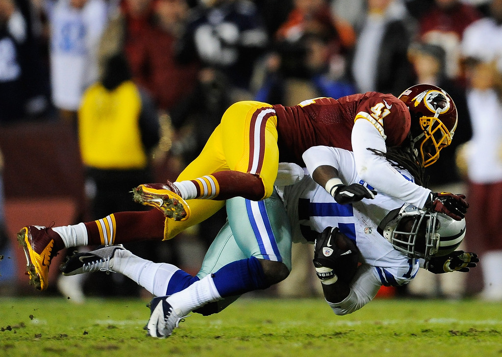 . LANDOVER, MD - DECEMBER 30:  Madieu Williams #41 of the Washington Redskins tackles Dwayne Harris #17 of the Dallas Cowboys after a pass reception in the second quarter at FedExField on December 30, 2012 in Landover, Maryland.  (Photo by Patrick McDermott/Getty Images)