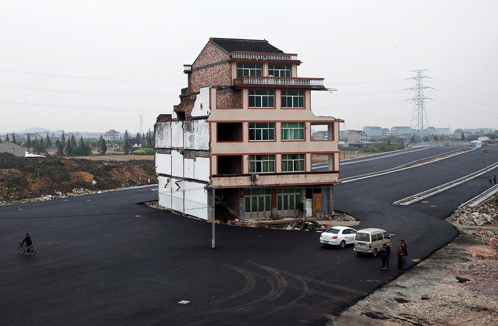 Description of . In this Nov. 22, 2012 file photo, people stand near a house sitting in the middle of a new main road on the outskirts of Wenling city in east China's Zhejiang province.  Authorities have demolished the five-story home that stood incongruously in the middle of a new main road and had become the latest symbol of resistance by Chinese homeowners against officials accused of offering unfair compensation. (AP Photo/File) CHINA OUT