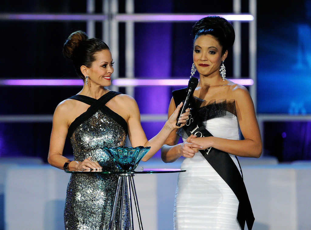 Description of . Host Brooke Burke Charvet (L) holds a microphone for Mariah Cary, Miss Iowa,  as she answers a question during the interview portion at the 2013 Miss America Pageant at PH Live at Planet Hollywood Resort & Casino on January 12, 2013 in Las Vegas, Nevada.  (Photo by David Becker/Getty Images)