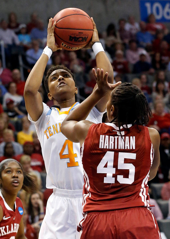 Description of . Tennessee guard Kamiko Williams (4) shoots over Oklahoma guard Jasmine Hartman (45) in the first half of a regional semifinal in the women's NCAA college basketball tournament in Oklahoma City, Sunday, March 31, 2013. (AP Photo/Sue Ogrocki)