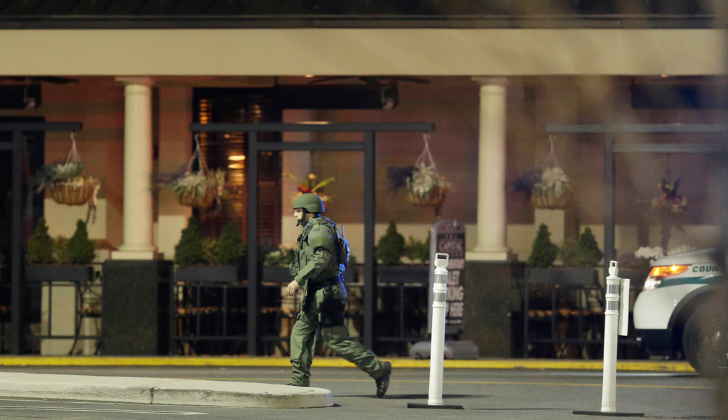 Description of . An official wearing tactical gear walks outside of Garden State Plaza Mall following reports of a shooter, Monday, Nov. 4, 2013, in Paramus, N.J. Hundreds of law enforcement officers converged on the mall Monday night after witnesses said multiple shots were fired there. (AP Photo/Julio Cortez)
