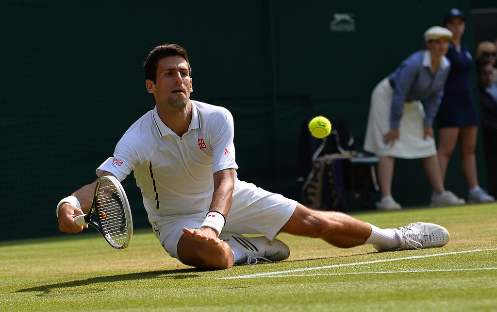 Description of . Serbia\'s Novak Djokovic dives as he returns against Argentina\'s Juan Martin Del Potro during their men\'s singles semi-final match on day eleven of the 2013 Wimbledon Championships tennis tournament at the All England Club in Wimbledon, southwest London, on July 5, 2013. CARL COURT/AFP/Getty Images