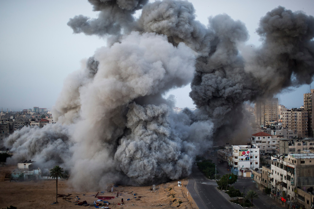 Description of . In this Nov. 18, 2012 file photo, smoke rises after an Israeli forces strike in Gaza City. This photo was one in a series of images by Associated Press photographer Bernat Armangue that won the first place prize in the World Press Photo 2013 photo contest for the Spot News series category.  (AP Photo/Bernat Armangue, File)