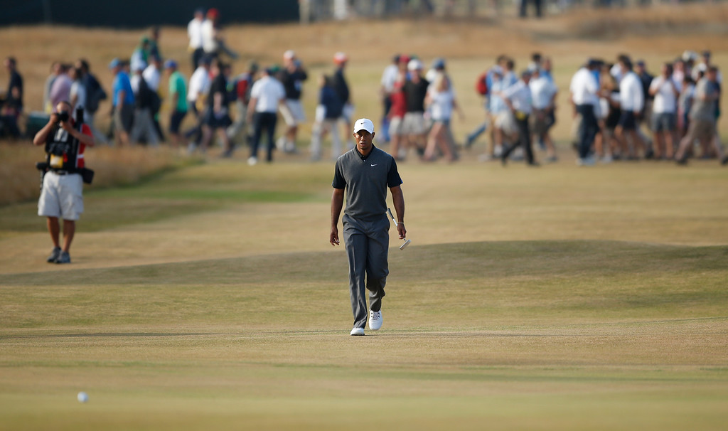 Description of . Tiger Woods of the United States walks up to the 18th green during the third round of the British Open Golf Championship at Muirfield, Scotland, Saturday July 20, 2013. (AP Photo/Matt Dunham)