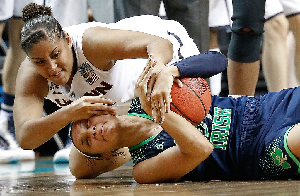Description of . Connecticut forward Kaleena Mosqueda-Lewis (23) and Notre Dame guard Kayla McBride (21) scramble for the ball during the first half of the championship game in the Final Four of the NCAA women's college basketball tournament, Tuesday, April 8, 2014, in Nashville, Tenn. (AP Photo/Mark Humphrey)