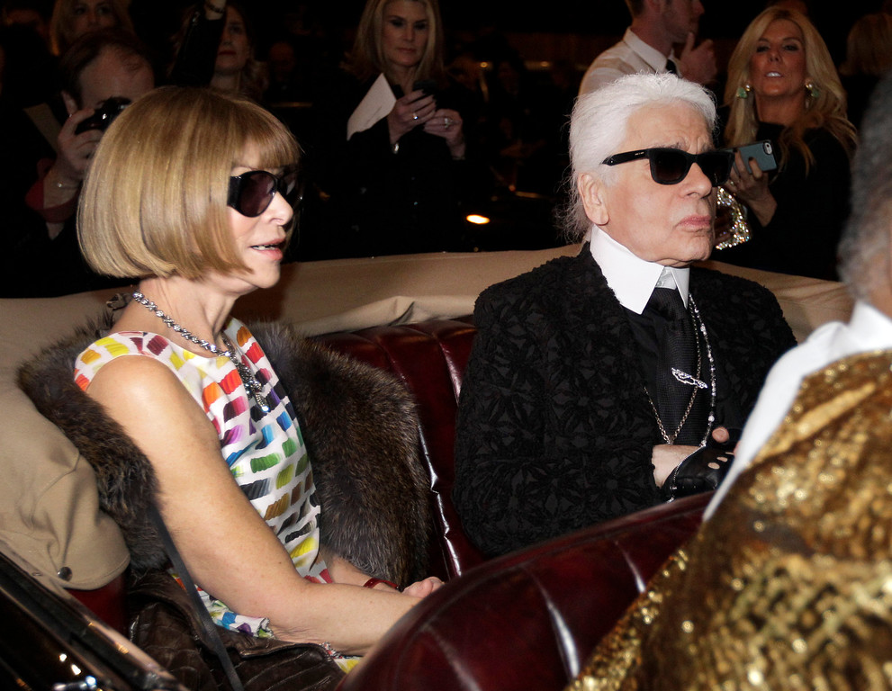 Description of . Anna Wintour, left, the english editor-in-chief of American Vogue and designer Karl Lagerfeld sit in a vintage car as they wait to view a movie short of Coco Chanel's return to fashion after closing her house during WWII before the start of Chanel's Metiers d'Art fashion show, Tuesday, Dec. 10, 2013, in Dallas. For more than a decade, designer Karl Lagerfeld has picked a city linked to the house for the theme of the show staged each December to highlight the work of its artisans. Fashion house founder Gabrielle