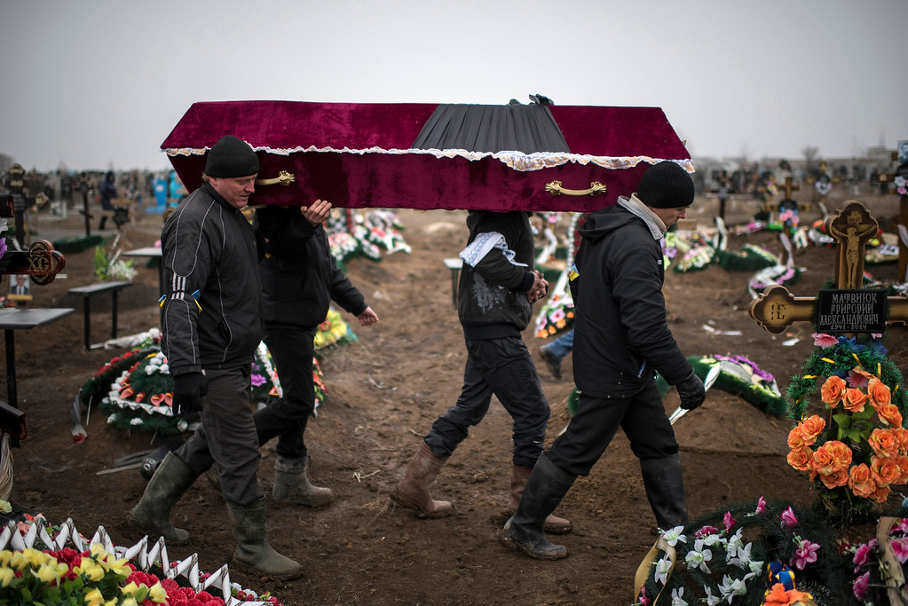 Description of . Ukrainian municipal woakers carry a coffin bearing the body of Vitaliy Sirotenko, who was killed Saturday during an attack in Mariupol, Ukraine, on  Tuesday Jan. 27, 2015. A lull in the fighting in December had raised hopes for a peaceful settlement, but hostilities have escalated again in recent weeks as the rebels launched a series of new offensives. Russia has blamed the renewed fighting on the Ukrainian side, saying it has tried to settle the conflict by force. (AP Photo/Evgeniy Maloletka)