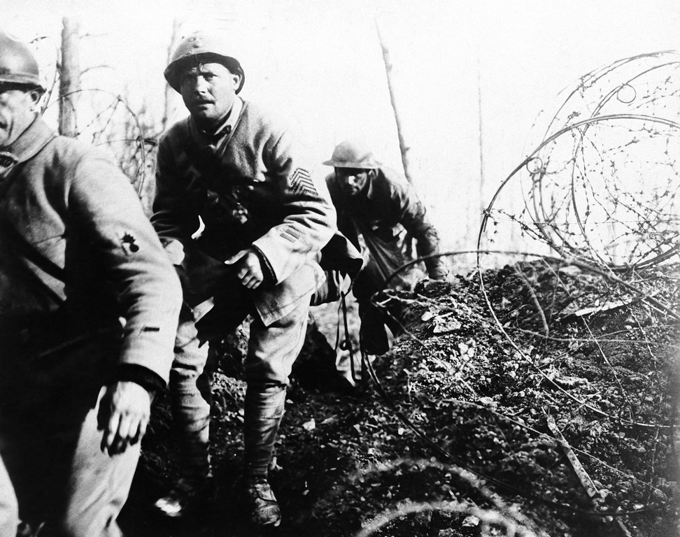 Description of . Two Frenchmen (in foreground) and an American soldier of the 168th infantry (originally Iowa National guardsman) coming over the top with sacks of hand grenades to harass the enemy in a French raid in 1919. (AP Photo)