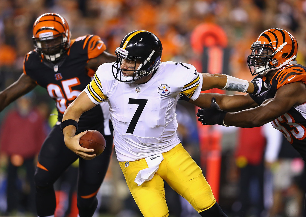 Description of . Ben Roethlisberger #7 of the Pittsburgh Steelers runs with the ball while defended by Michael Johnson #93 of the Cincinnati Bengals during the game at Paul Brown Stadium on September 16, 2013 in Cincinnati, Ohio.  (Photo by Andy Lyons/Getty Images)