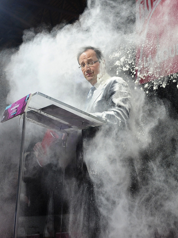 ". In this Feb. 1, 2012 file photo, an unidentified woman throws flour on French Socialist Party candidate for the 2012 presidential elections, Francois Hollande, in Paris. The woman ran to the side of the podium where Hollande stood to sign a ""social contract\"" in favor of housing for all.  (AP Photo/SZG, File)"