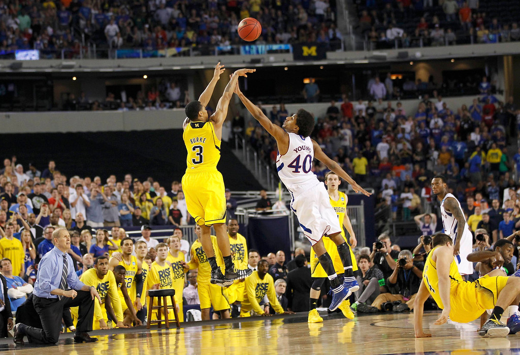 Description of . Michigan Wolverines guard Trey Burke shoots a three point basket over Kansas Jayhawks forward Kevin Young to tie the game during the second half in their South Regional NCAA men\'s basketball game in Arlington, Texas March 29, 2013.  REUTERS/Mike Stone