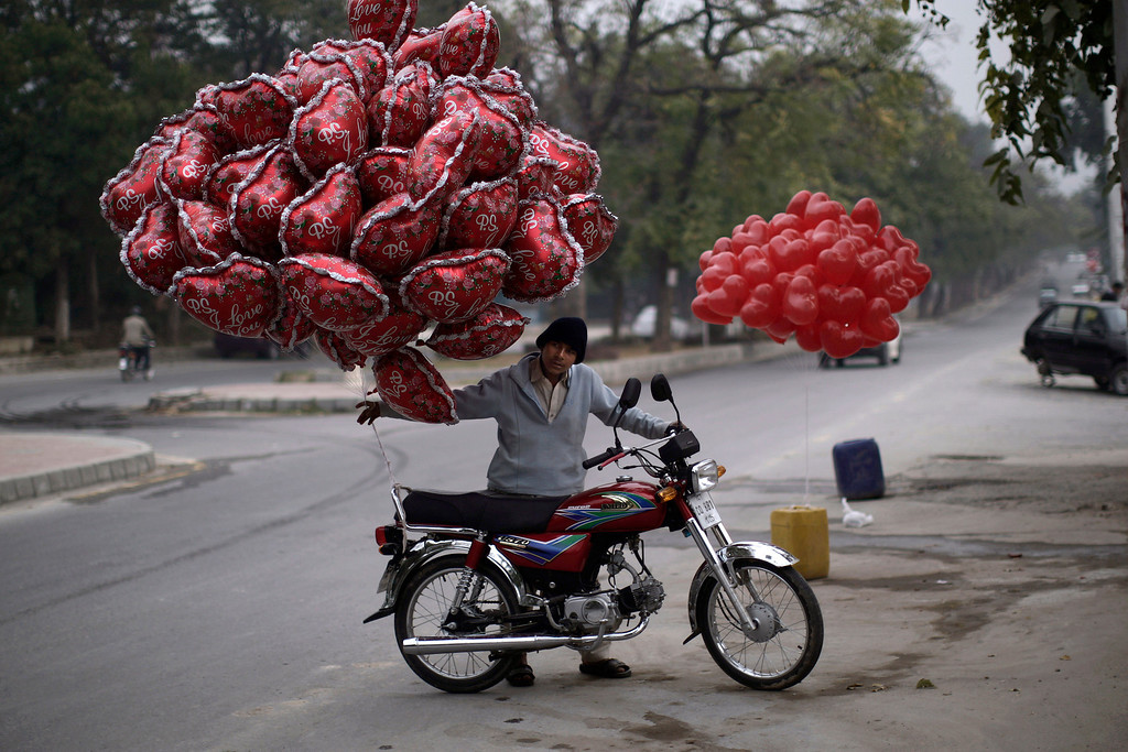 Description of . A Pakistani youth pushes his motorcycle, with balloons that he hopes to sell on Valentine's Day, in Islamabad, Pakistan, Thursday, Feb. 14, 2013. (AP Photo/Muhammed Muheisen)
