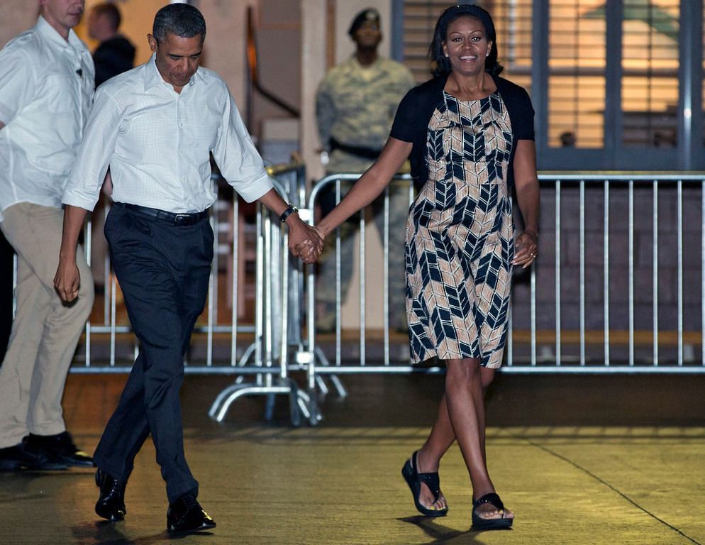 Description of . President Barack Obama and first lady Michelle Obama walk across the tarmac to board Air Force One at Honolulu Joint Base Pearl Harbor-Hickam, Saturday, Jan. 5, 2013, in Honolulu, en route to Washington after their holiday vacation.  (AP Photo/Carolyn Kaster)