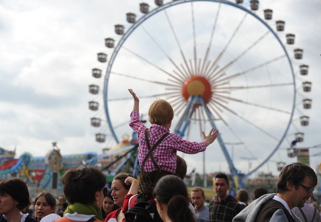Description of . A little boy dressed in traditional Bavarian clothes sits on his father's shoulders and reacts as he sees the ferris wheel at the Oktoberfest beer festival at the Theresienwiese in Munich, southern Germany on September 21, 2013. The traditional Bavarian beer festival runs from September 21 - October 6, 2013.  AFP PHOTO / DPA/ ANDREAS GEBERT/AFP/Getty Images