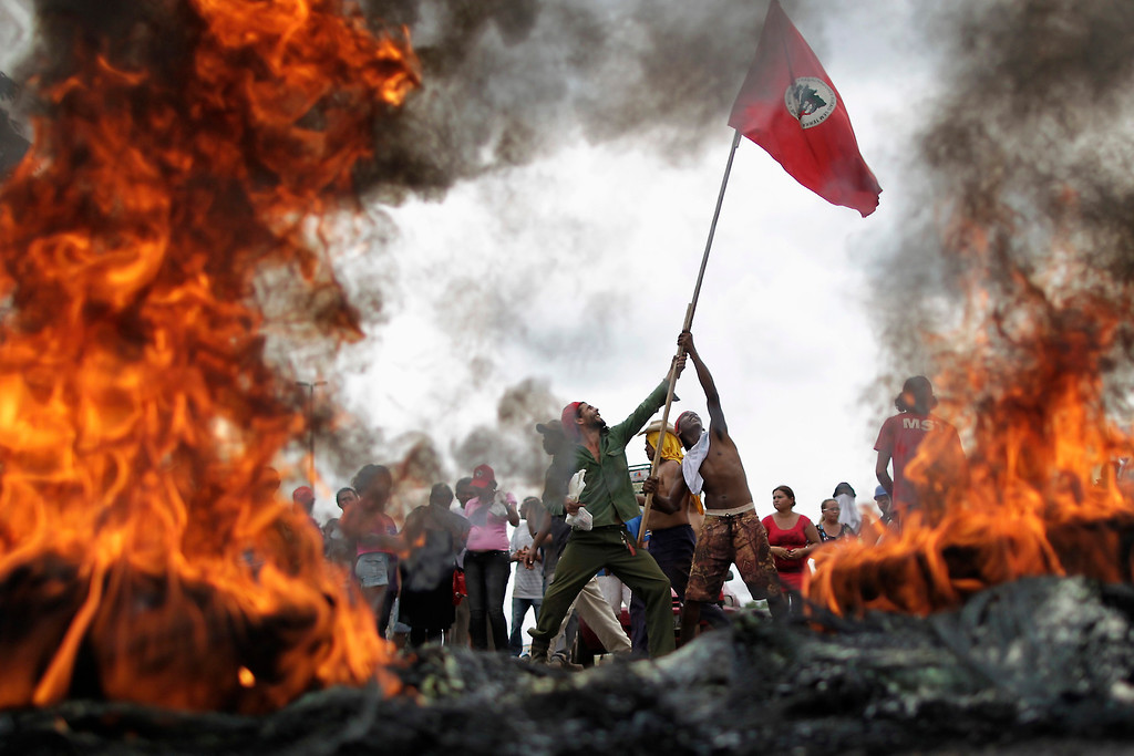 Description of . Members of the Movement of Landless Rural Workers (MST), who are protesting for change in the process of land reform, hold a flag up by burning tires on a highway in Brasilia November 21, 2012. REUTERS /Ueslei Marcelino