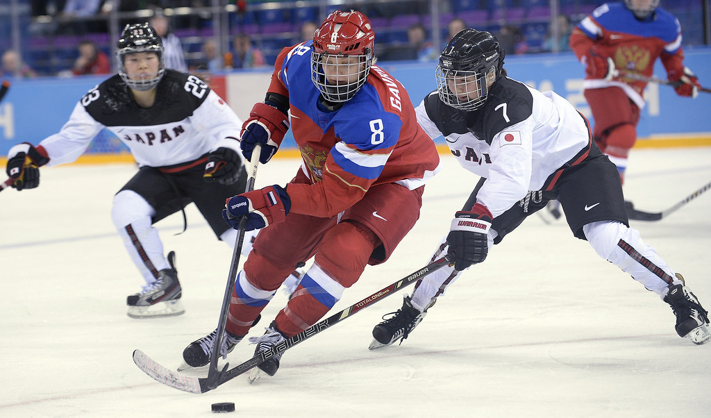 Description of . Russia's Iya Gavrilova (C) vies with Japan's Mika Hori (R) and Japan's Ami Nakamura (L) during the Women's Ice Hockey Group B match Russia vs Japan at the Shayba Arena during the Sochi Winter Olympics on February 11, 2014.  ALEXANDER NEMENOV/AFP/Getty Images