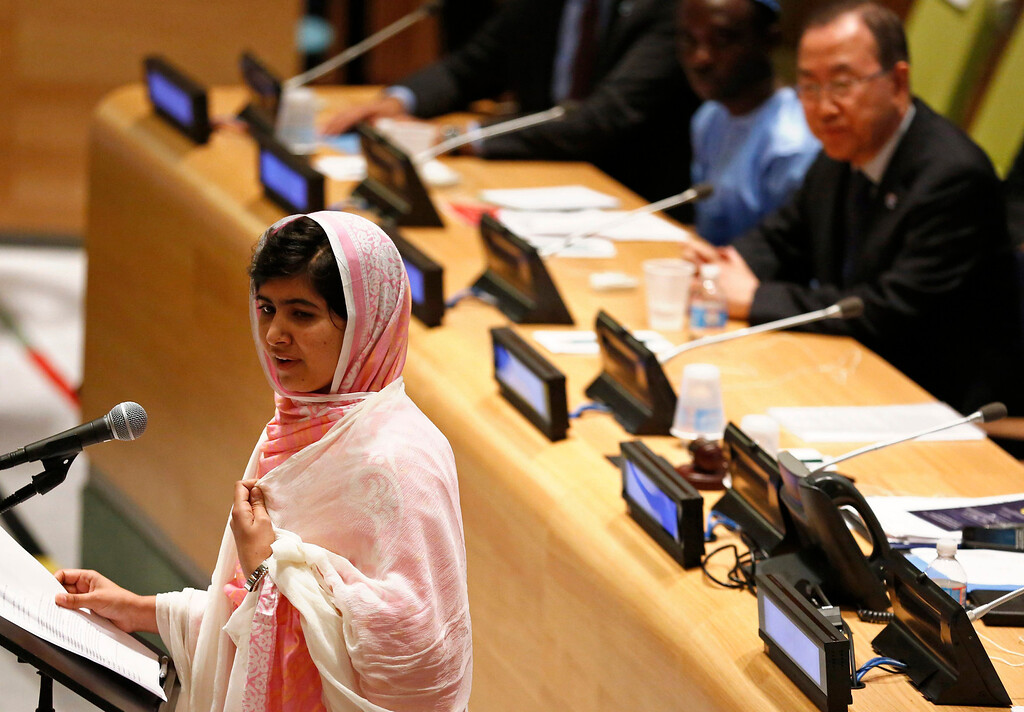 Description of . Malala Yousafzai (L) gives her first speech since the Taliban in Pakistan tried to kill her for advocating education for girls, at the United Nations Headquarters in New York, July 12, 2013. Wearing a pink head scarf, Yousafzai told U.N. Secretary-General Ban Ki-moon (top R) and nearly 1,000 students from around the world attending a Youth Assembly at U.N. headquarters in New York that education was the only way to improve lives. REUTERS/Brendan McDermid