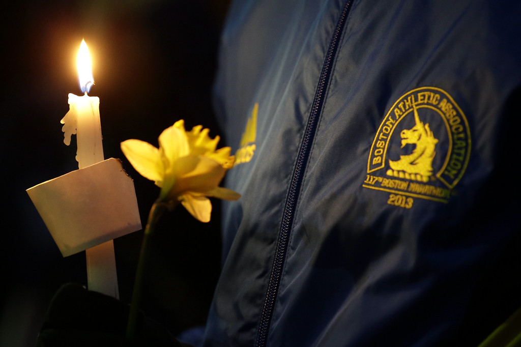 Description of . Lizzie Lee, 56, of Lynwood, Wash., who was participating in her first Boston Marathon and 11th overall, holds a candle and a flower at Boston Common during a vigil for the victims of the Boston Marathon explosions, Tuesday, April 16, 2013, one day after bombs exploded at the finish line of the Boston Marathon. (AP Photo/Julio Cortez)