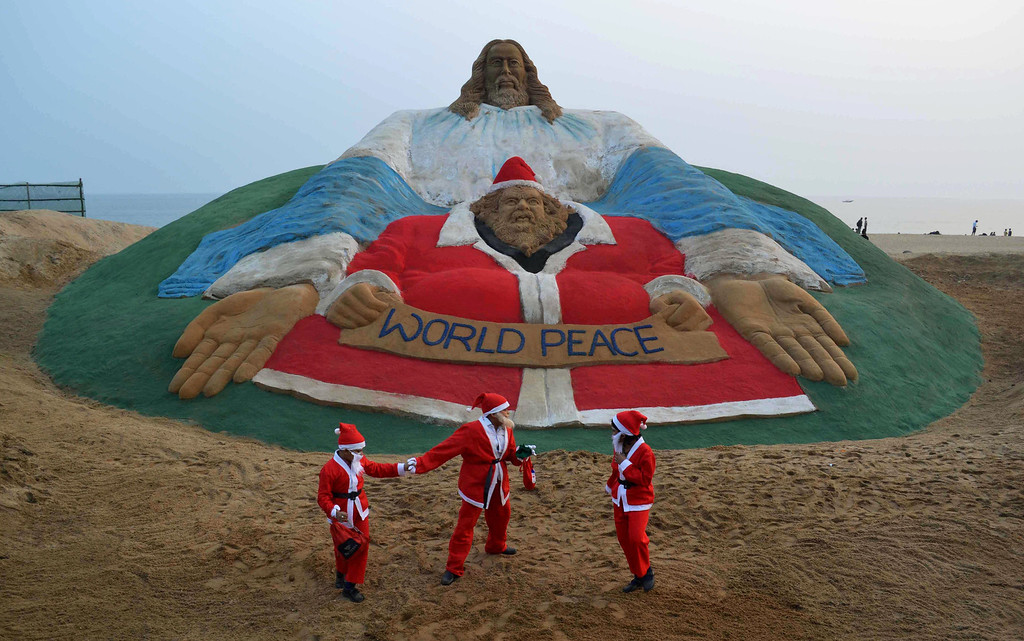 Description of . Indian children dressed as Santa Claus play near a sand sculpture depicting God and Jesus Christ, and created by sand artist Sudarsan Pattnaik, at Golden Sea Beach in Puri, some 65 kms away from Bhubaneswar on December 24, 2013. Despite Christians forming a little over 2 percent of the billion plus population in India, with Hindus comprising the majority, Christmas is celebrated with much fanfare and zeal throughout the country.  ASIT KUMAR/AFP/Getty Images
