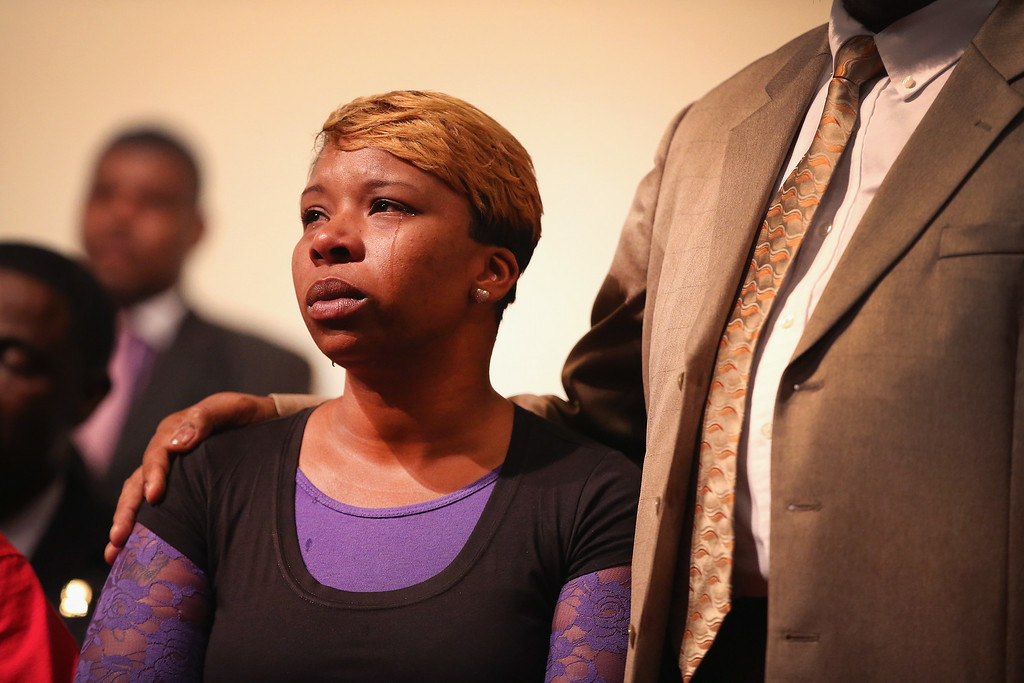 Description of . ST. LOUIS, MO - AUGUST 12:  A tear rolls down the cheek of Lesley McSpadden, the mother of slain teenager Michael Brown, during a community meeting held at Greater St. Marks Family Church to discuss the killing of her son and the civil unrest resulting from his death on August 12, 2014 in St Louis, Missouri. Brown was shot and killed by a police officer on Saturday in the nearby suburb of Ferguson. Ferguson has experienced two days of violent protests since the killing but, tonight the town remained mostly peaceful.  (Photo by Scott Olson/Getty Images)