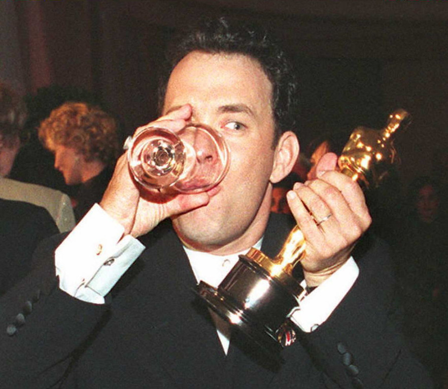 Description of . US actor Tom Hanks holds up his Oscar as he drinks a glass of water while attending the Governor's Ball after the 67th annual Academy Awards in Los Angeles 27 March. Hanks won as best actor for his role in the film