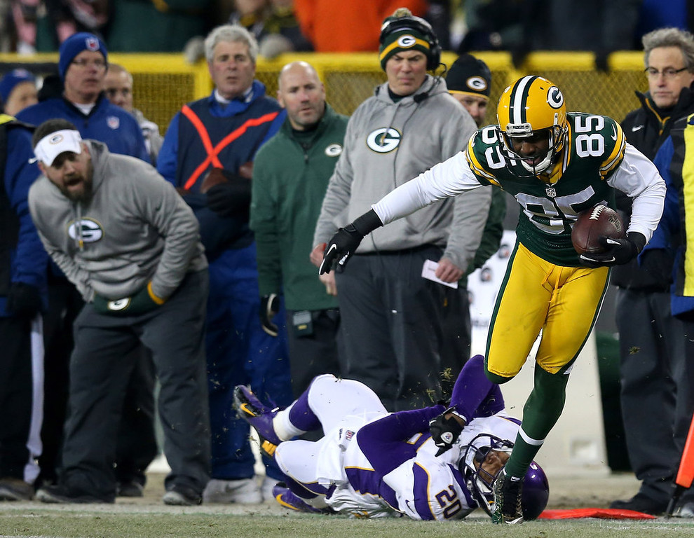 Description of . Wide receiver Greg Jennings #85 of the Green Bay Packers breaks a tackle by cornerback Chris Cook #20 of the Minnesota Vikings to run for 32-yards in the first half during the NFC Wild Card Playoff game at Lambeau Field on January 5, 2013 in Green Bay, Wisconsin.  (Photo by Jonathan Daniel/Getty Images)