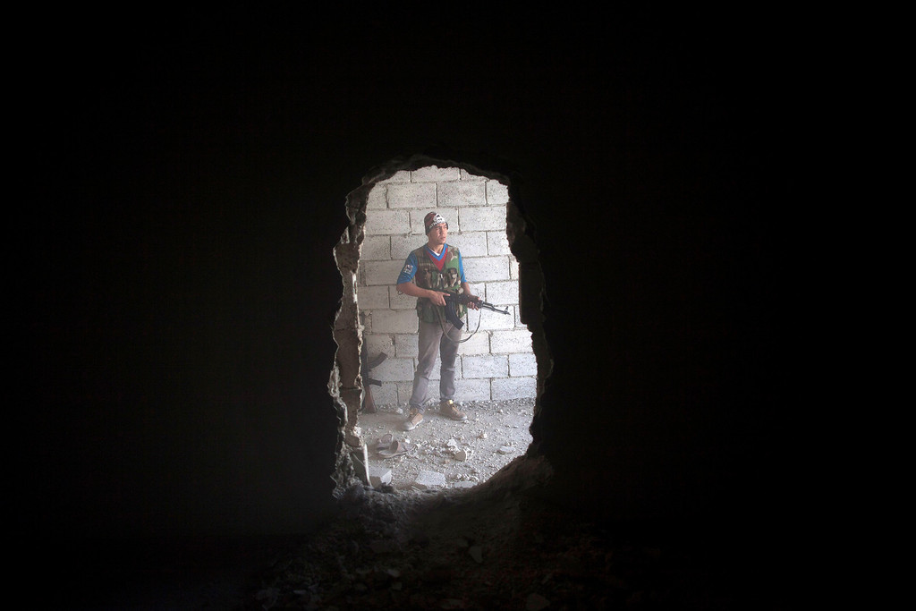 Description of . FILE - A Free Syrian Army fighter takes cover in a building during clashes against the Syrian Army in Aleppo, Syria, Tuesday, Sept. 25, 2012. (AP Photo/Manu Brabo, File)