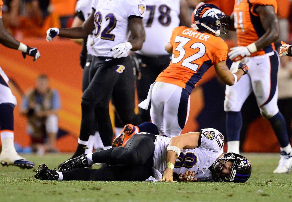 Description of . Baltimore Ravens tight end Dallas Clark (87) lays on the ground after a hard hit. The Denver Broncos took on the Baltimore Ravens in the first game of the 2013 season at Sports Authority Field at Mile High in Denver on September 5, 2013. (Photo by AAron Ontiveroz/The Denver Post)