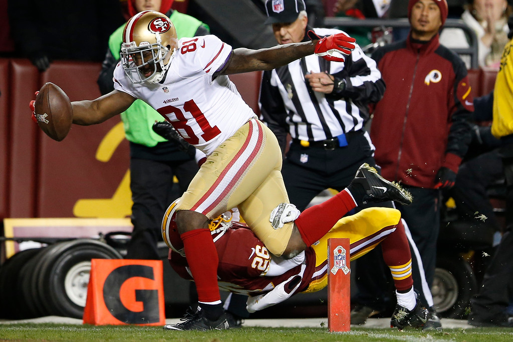 Description of . San Francisco 49ers wide receiver Anquan Boldin lands in the end zone with a touchdown pass as Washington Redskins cornerback Josh Wilson hits the turf during the first half of an NFL football game in Landover, Md., Monday, Nov. 25, 2013. (AP Photo/Evan Vucci)