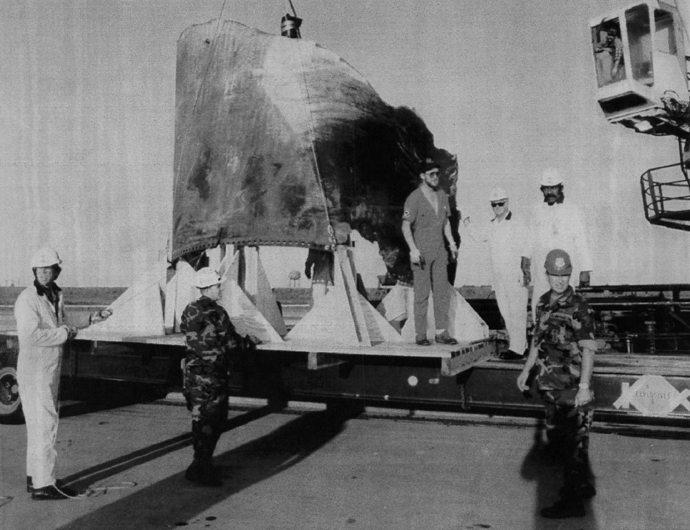 Description of . Workers unload a 10 by 20 foot piece of shuttle Challenger\'s right hand solid rocket booster on April 15, 1986 at Port Canaveral. The piece of SRB is believed to be at the joint where burn-through occurred dooming the Challenger.   Denver Post Library Archive