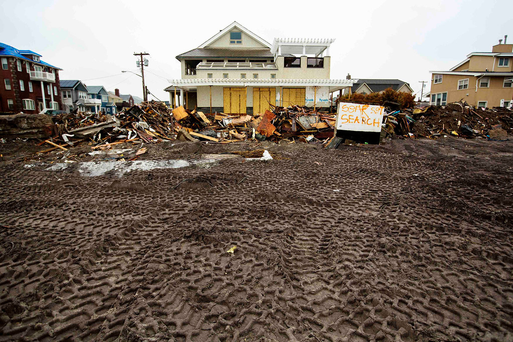 Description of . Tire tracks from heavy machinery are seen in the sand in front of homes damaged during Superstorm Sandy in the Queens borough region of the Rockaways in New York November 27, 2012.  REUTERS/Lucas Jackson