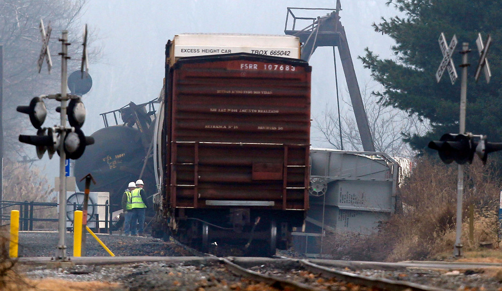 Description of . Officials stand next to derailed freight train cars in Paulsboro, N.J., Friday, Nov. 30, 2012. People in three southern New Jersey towns were told Friday to stay inside after the freight train derailed and several tanker cars carrying hazardous materials toppled from a bridge and into a creek. At least one tanker car may contain vinyl chloride, Gloucester County Emergency Management director J. Thomas Butts told WPVI-TV. (AP Photo/Mel Evans)