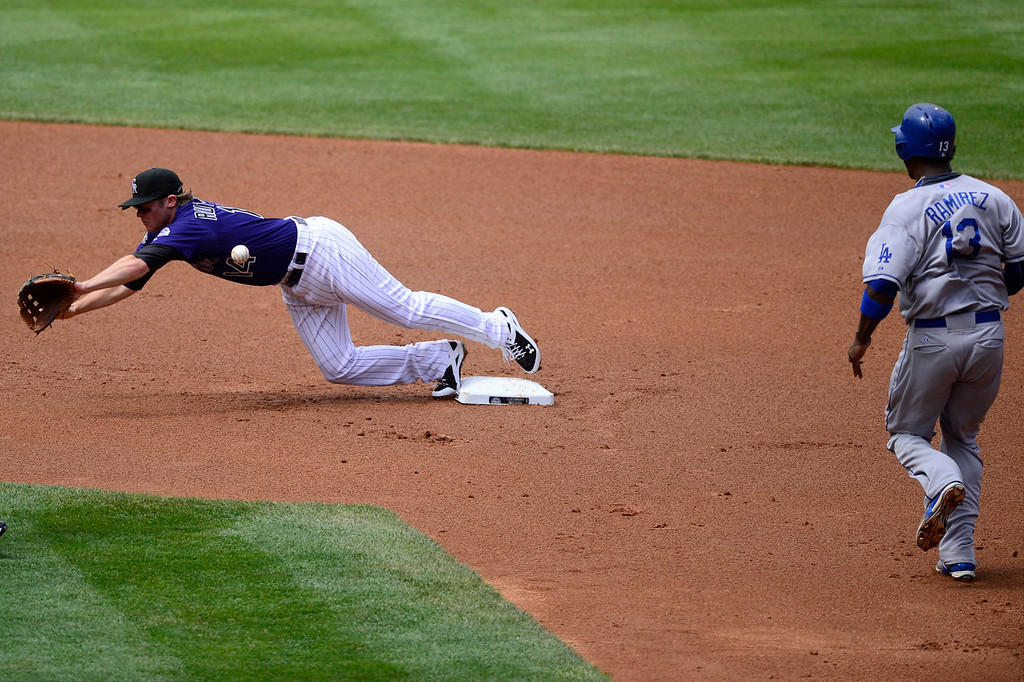 Description of . Josh Rutledge (14) of the Colorado Rockies attempts to wrangle a wild throw from Jordan Pacheco (15) as Hanley Ramirez (13) of the Los Angeles Dodgers runs safely towards second base during the action in Denver on Monday, September 2, 2013. The Colorado Rockies hosted the Los Angeles Dodgers at Coors Field.   (Photo by AAron Ontiveroz/The Denver Post)