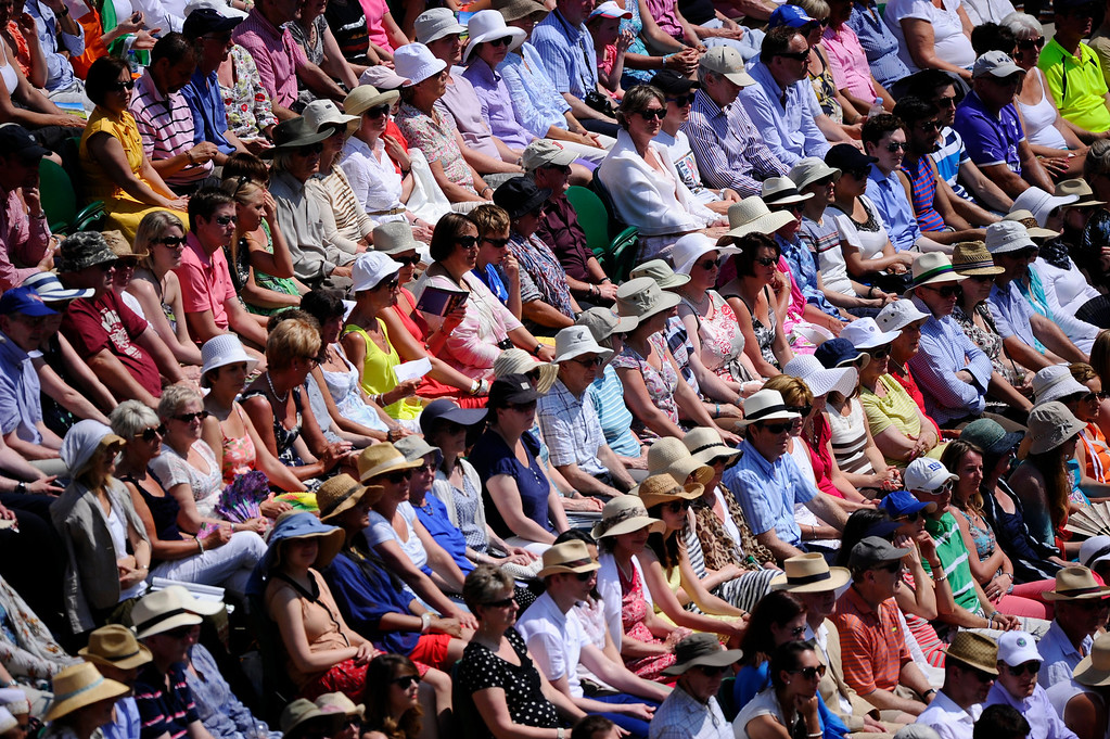 Description of . The crowd on Centre Court sit in the sun as Sabine Lisicki of Germany plays Marion Bartoli of France during the Women's singles final match at the All England Lawn Tennis Championships in Wimbledon, London, Saturday, July 6, 2013. (AP Photo/Adrian Dennis, Pool)