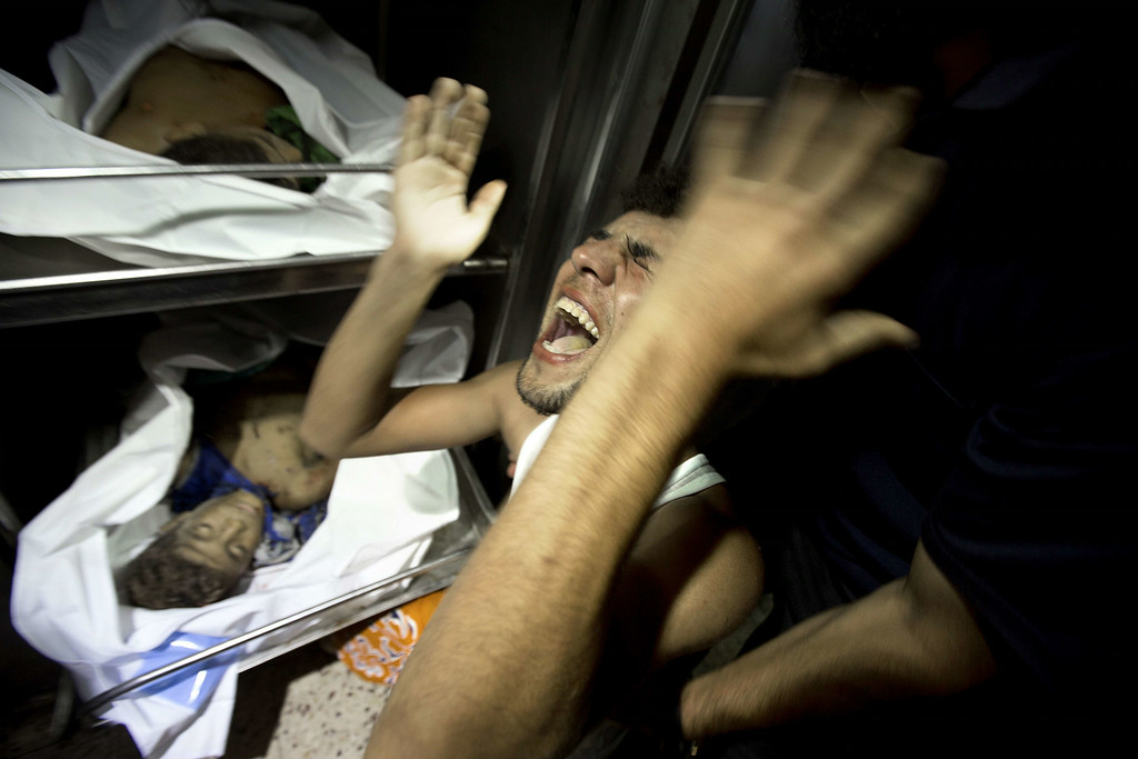 Description of . A relatives of four Palestinian boys, all from the Bakr family, mourns over the body of one of the boys at the morgue of al-Shifa hospital in Gaza City, on July 16, 2014. Four children were killed and several injured at a beach in Gaza City medics said, in Israeli shelling witnessed by AFP journalists. The strikes appeared to be the result of shelling by the Israeli navy against an area with small shacks used by fishermen. The deaths raised the overall toll in nine days of violence in Gaza to 213. AFP PHOTO / MAHMUD HAMS/AFP/Getty Images