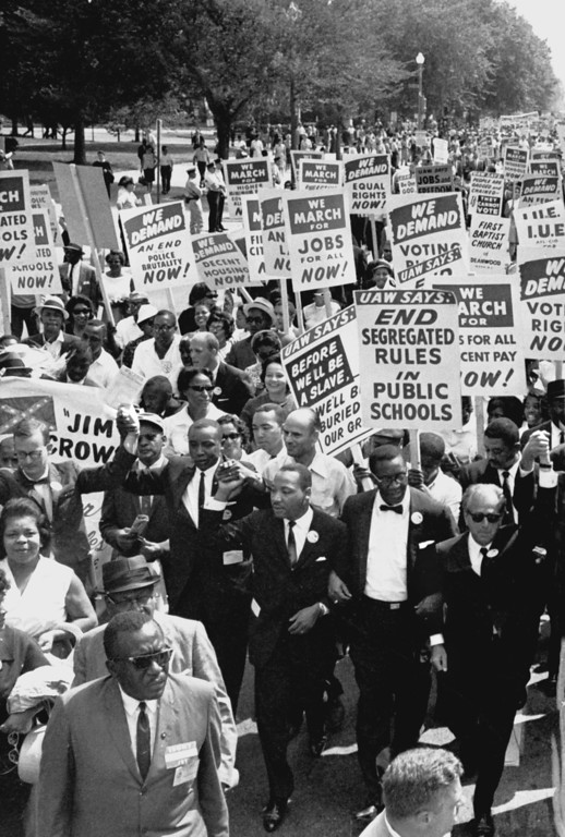 Description of . Dr. Martin Luther King, Jr., third from left, marches in a line of men with arms linked during the March on Washington for civil rights on August 28, 1963.  (AP Photo)