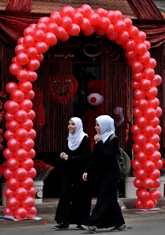 Description of . Palestinian girls walk in front of a shop decorated for Valentine's Day, in Gaza City, Thursday, Feb. 14, 2013. Valentine's Day is a festival of romantic love and is celebrated in many countries over the world by giving cards, flowers or gifts to spouses or partners. (AP Photo/Adel Hana)