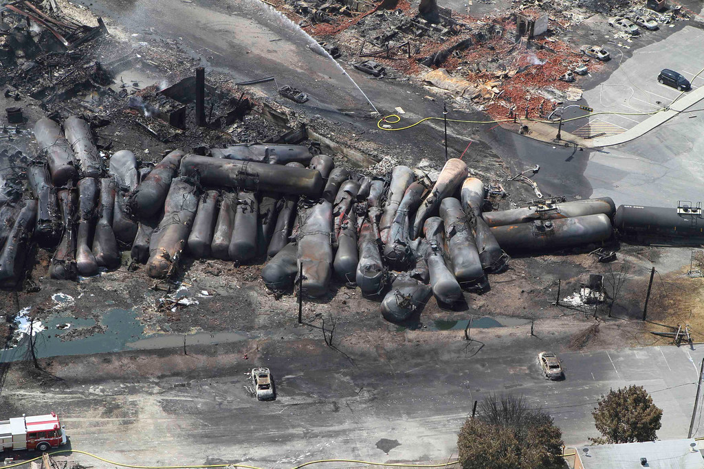 Description of . An aerial view of burnt train cars after a train derailment and explosion in Lac-Megantic, Quebec July 8, 2013, in this picture provided by the Transportation Safety Board of Canada.  REUTERS/Transportation Safety Board of Canada/Handout via Reuters