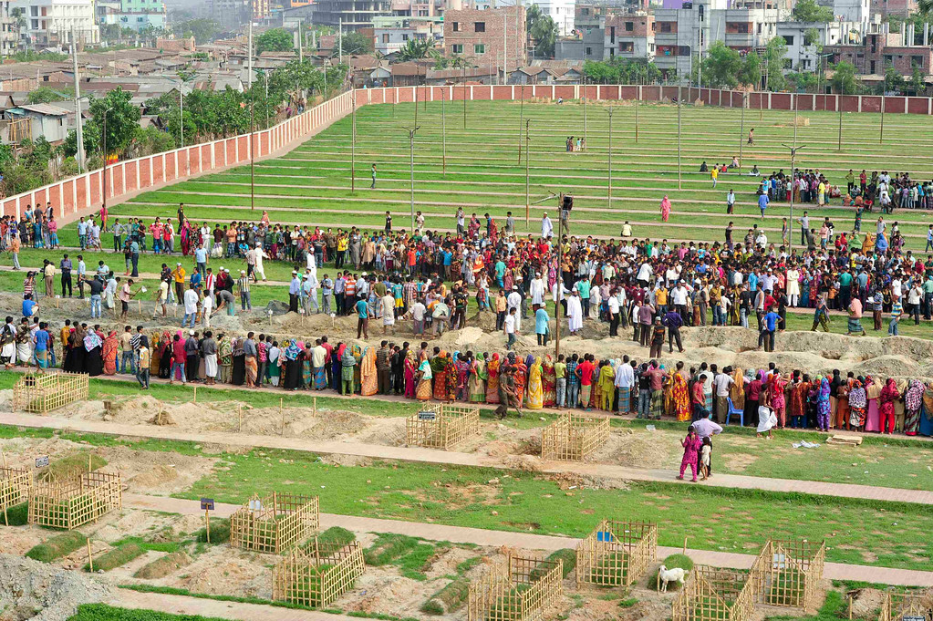 Description of . People gather during a mass burial of unidentified garment workers, who died in the collapse of the Rana Plaza building in Savar, in Dhaka May 1, 2013. REUTERS/Khurshed Rinku