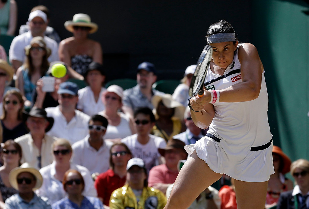 Description of . Marion Bartoli of France returns to Sabine Lisicki of Germany during their Women's singles final match at the All England Lawn Tennis Championships in Wimbledon, London, Saturday, July 6, 2013. (AP Photo/Anja Niedringhaus)
