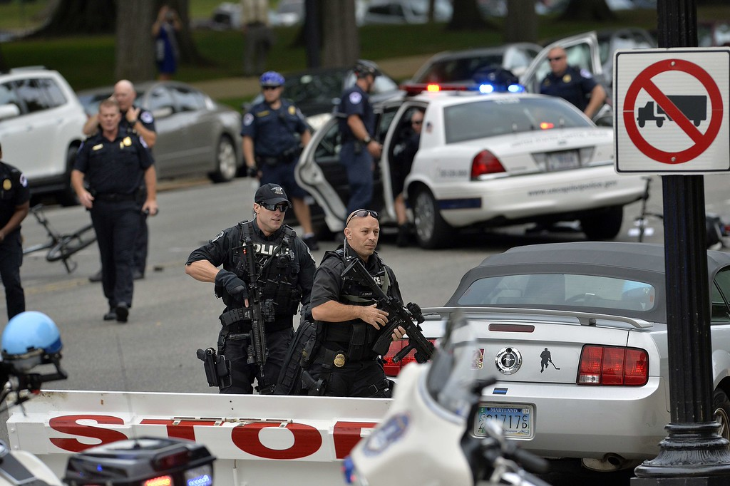 Description of . Police run after shots fired were reported near 2nd Street NW and Constitution Avenue on Capitol Hill in Washington, DC, on October 3, 2013.  The US Capitol was placed on security lockdown Thursday after shots were fired outside the complex, senators said.