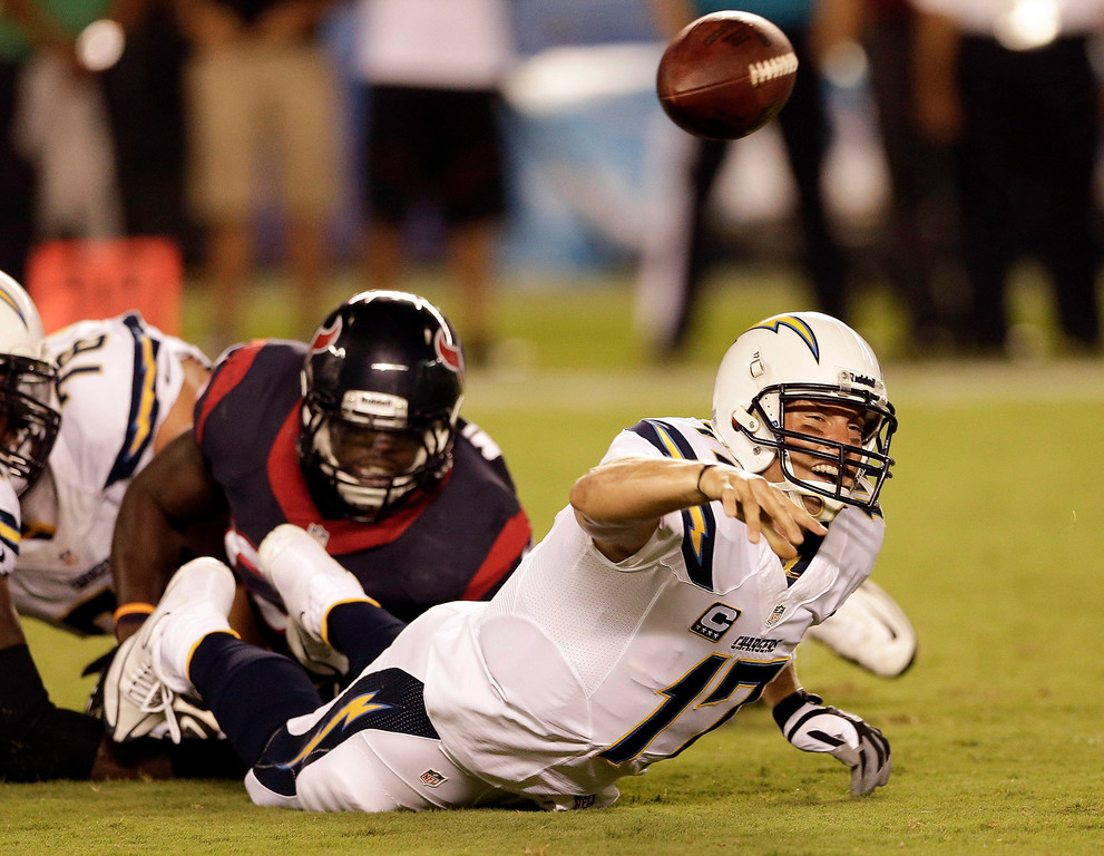 Description of . San Diego Chargers quarterback Philip Rivers, right, throws under pressure from Houston Texans outside linebacker Whitney Mercilus during the first half of an NFL football game Monday, Sept. 9, 2013, in San Diego. (AP Photo/Gregory Bull)