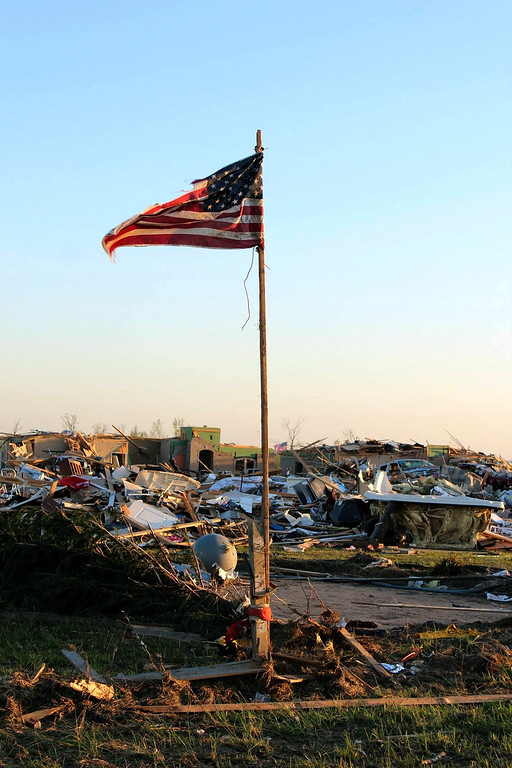 Description of . In this handout provided by the Arkansas National Guard, an American flag stands amongst the rubble of a community following a deadly tornado April 28, 2014 in Vilonia, Arkansas.  (Photo by Arkansas National Guard via Getty Images)
