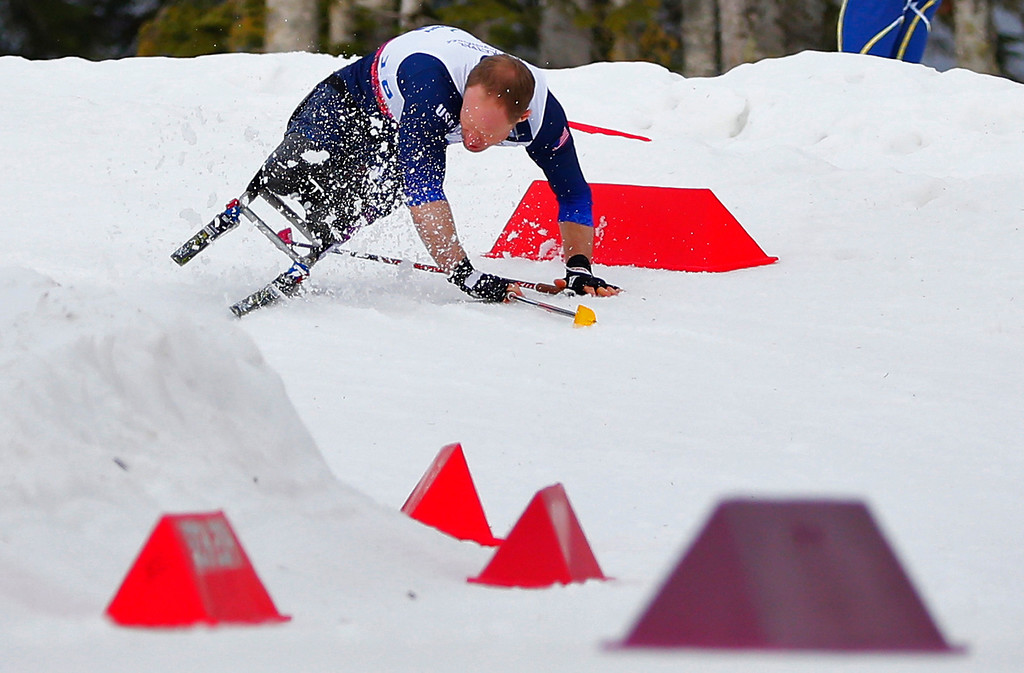 Description of . Daniel Cnossen of the United States crashes during the men's 15-kilometer cross country ski sitting event at the 2014 Winter Paralympics, Sunday, March 9, 2014, in Krasnaya Polyana, Russia. (AP Photo/Dmitry Lovetsky)